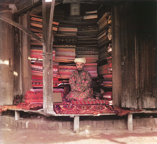 This photograph from the Library of Congress, focuses on a fabric merchant in Samarkand, surrounded by brightly colored merchandise.
