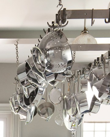 Pots and pans can take up a lot of space on your counters and in your cabinets. Remedy that with a pot hanger like this one in Martha's kitchen.