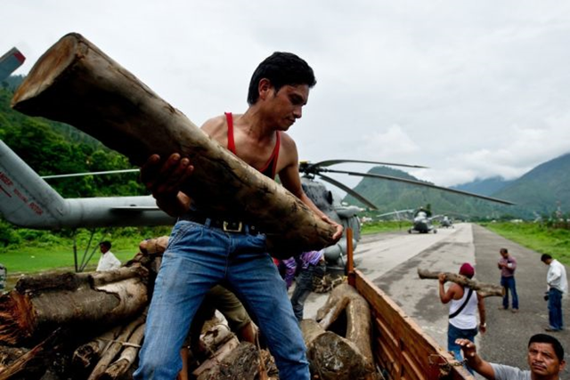 Indian workers offload wood, to be carried to Kedarnath by the Indian Air Force for cremation preparations, at Gauchar Airfield in Uttarakhand state on 25 June 2013. Around 1,000 people have been killed in flash floods and landslides in northern India. Photo: Global Post