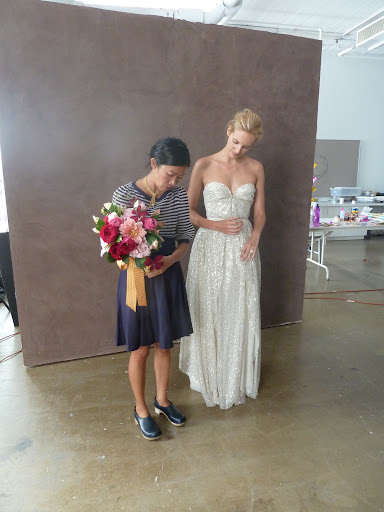 Kate on set showing our model the best way to hold the bouquet.