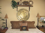 This huge brass table sits above Lynda's bed. She bought two of them with stands for a coffee table. Grand total = $20!