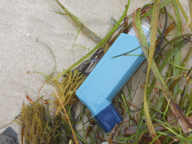 A discarded asthma inhaler that has washed up on a beach. mikecogh / flickr