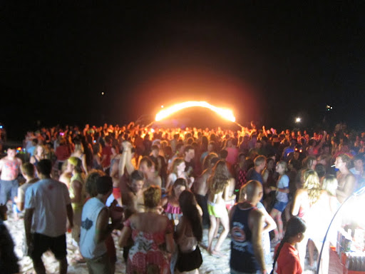 Party people on the beach with a burning jumprope visible in background.