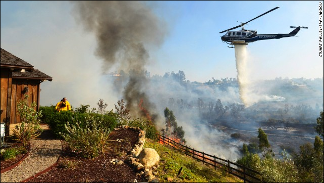 A helicopter drops water near the Rancho Santa Fe neighborhood of San Diego on Tuesday, 13 May 2014. Photo: Stuart Palley / EPA / LANDOV