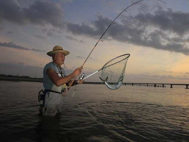 Coalition to Restore Coastal Louisiana volunteer Al DuVernay, 61, catches a fish along the shore line in Grand Isle, La. He volunteers to help rebuild beaches. Photo: Sean Gardner / USA TODAY