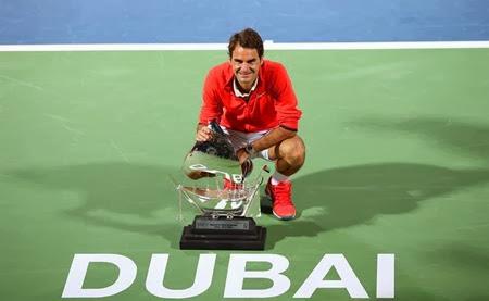 Federer posando junto al trofeo tras ganar el ATP de Dubai 2014