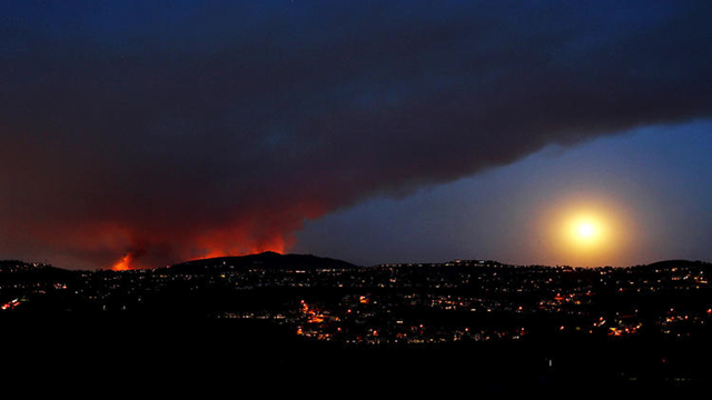 The Cocos fire burns in San Marcos as the moon rises in a smoky sky as seen from Carlsbad, California, 15 May 2014. Photo: Luis Sinco / Los Angeles Times