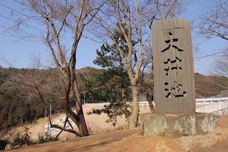 石碑と下流側の堤体を望む