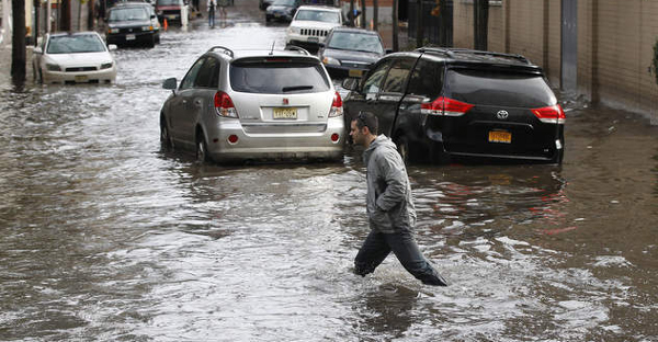 A man walks along the street as 2 automobiles are caught in the waters as the rescue by the National Guard continues after Hurricane Sandy Hoboken, New Jersey, 31 October 2012. Photo: William Perlman / The Star-Ledger