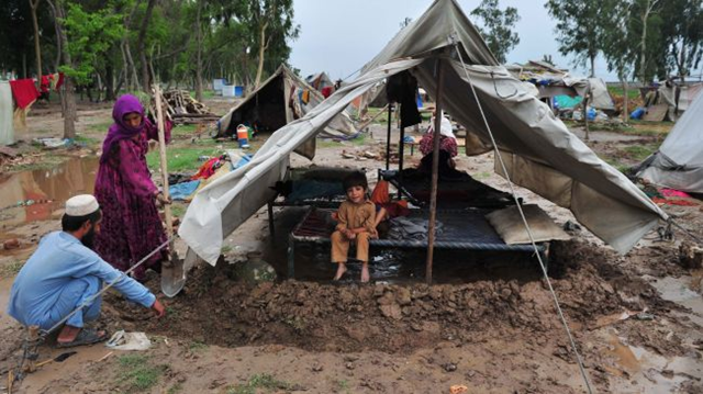 A refugee family, who survived 2010 flooding, dig a moat around their tent at a camp in Nowshera, Pakistan on 26 July 2011. presstv.ir