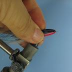 Teraz przeginamy cały przywiązany materiał do tyłu. Ostrożnie dociskamy palcami materiał w miejscu gdzie nałożony został klej. Ta operacja powinna wstępnie uformować kształt muchy.
