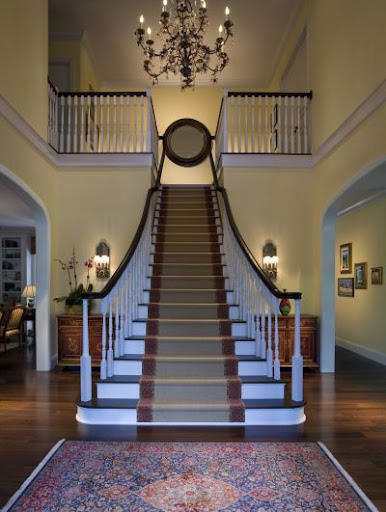 The dramatic staircase, warm lighting and oriental rug make this entryway so welcoming. (Elle Decor)