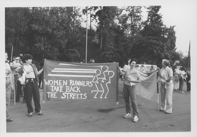 Women Runners hold up a Take Back the Streets sign at the Women Take Back the Night march. April 19, 1980.