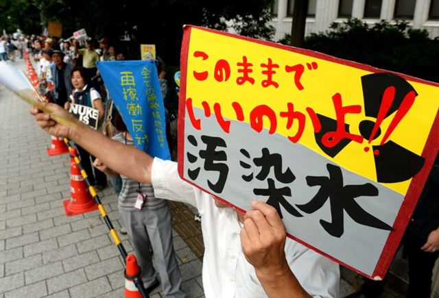 A protester calls for measures to contain contaminated water at the Fukushima No. 1 nuclear power plant during a demonstration in front of the prime minister's office on 2 August 2013. Photo: Satoru Ogawa / Asahi Shimbun