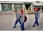 Tibetan students from the Tibetan SOS Children's Village walk home after school past some political signs in Choglamsar, Ladakh, India. <em>© Paula Bronstein</em>