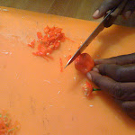 Finely chop the hot peppers by holding on to the stem and cutting the rest with your other hand (Haitian food)