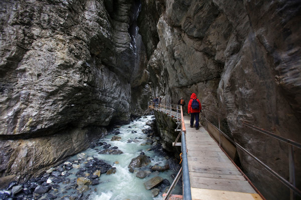 Tourists walking along a stream originating from the Lower Grindelwald Glacier in Switzerland. The glacier once extended through the gorge. Photo Christoph Bangert / The New York Times