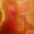 """Ekskluzywna tkanina typu """"tafta"""". Motyw roślinny - liście. Na zasłony, poduszki, narzuty, dekoracje. Szeroka. Czerwona, pomarańczowa, złota."""