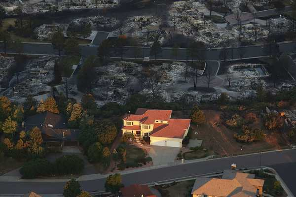 Destroyed homes sit beside a home left untouched by fire in a neighborhood affected by the Waldo Canyon fire on 30 June 2012 in Colorado Springs, Colorado. Spencer Platt / Getty Images