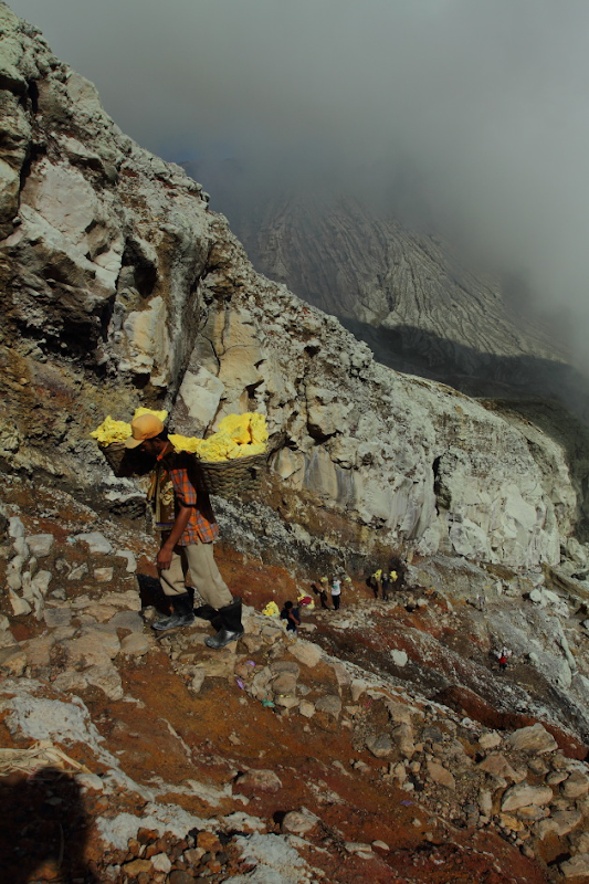 The steep and narrow climb with the sulphur load from the Ijen Crater, Indonesia