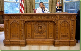President Barack Obama sits behind the Resolute Desk in the Oval Office during a conference call with people of faith, August 19, 2009.  Official White House Photograph by Pete Souza.&#10;&#10;This official White House photograph is being made available only for publication by news organizations and/or for personal use printing by the subject(s) of the photograph. The photograph may not be manipulated in any way and may not be used in commercial or political materials, advertisements, emails, products, promotions that in any way suggests approval or endorsement of the President, the First Family, or the White House. 