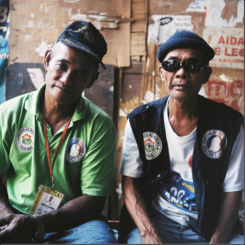 Portrait of the keppers of peace and security of Happyland, a large garbage dump in Manila. Most of the residents of Happyland collect recyclable materials such as plastics, bottles, and metal parts where they exchange them at nearby junk shops. They also salvage any wood from the dump and nearby construction sites for the charcoal makers to produce charcoal from. Scavengers earn a measly eighty pesos (USD 2.00) for a day's work while the charcoal makers are better off with two hundred pesos (USD 5.00).