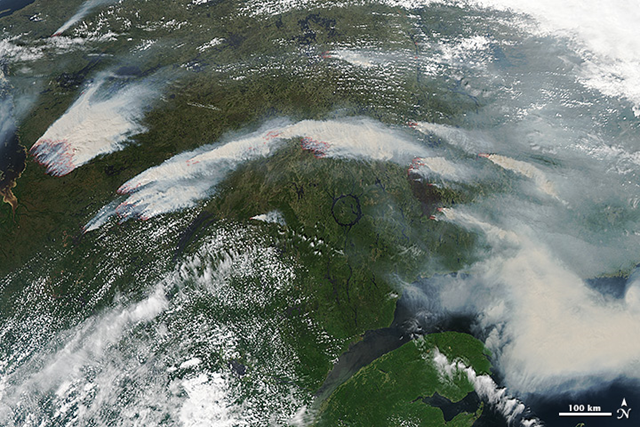 On 4 July 2013, the Moderate Resolution Imaging Spectroradiometer (MODIS) on NASA's Aqua satellite captured this image of wildfires burning in western Quebec near James Bay. Red outlines indicate hot spots where MODIS detected unusually warm surface temperatures associated with fire. Photo: NASA