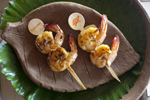 We presented these skewered Carib sugar-cane shrimp on local pottery. A water-lily pad lined the charger.