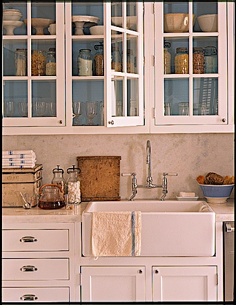 Painting the inside of glass front cabinets is another a great way to add color to a room.  In this kitchen, the blue background highlights the contents of the cabinets.