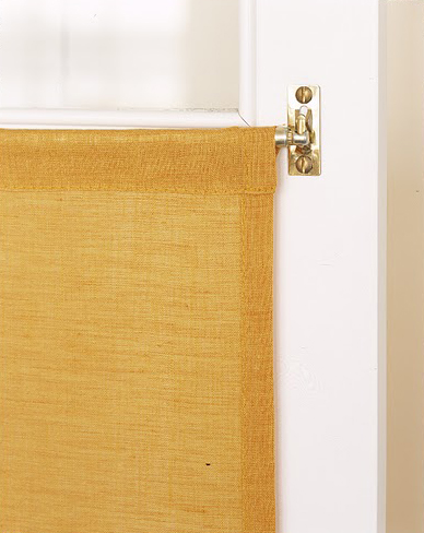 To hide glass-cabinet contents, create miniature curtains in a color that goes well with your kitchen decor. All you need to do is custom sew a curtain and install a small curtain rod on the inside of the door.