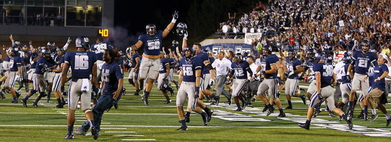 Utah State players storm the field after beating the University of Utah in Logan