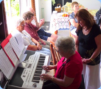 Barbara Powell trying out the Korg whilst our host, Delyse Whorwood, watches on and enjoying Barbara's playing.