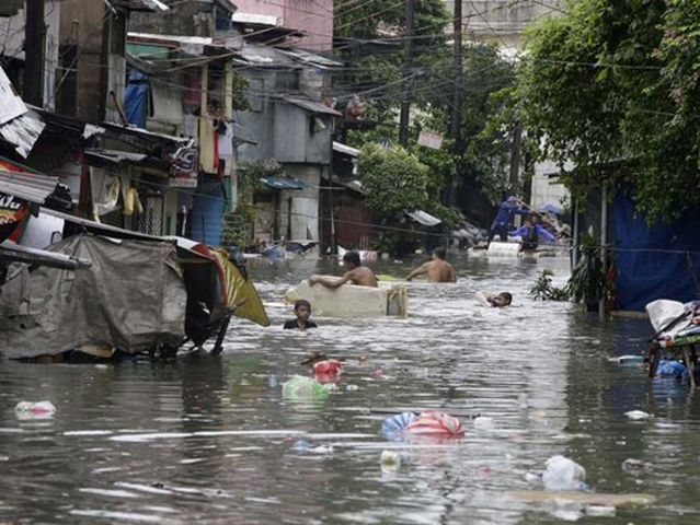 Residents wade through a flooded street full of floating garbage north east of Manila, in the Philippines, on 23 September 2013. Photo: Bullit Marquez / AP