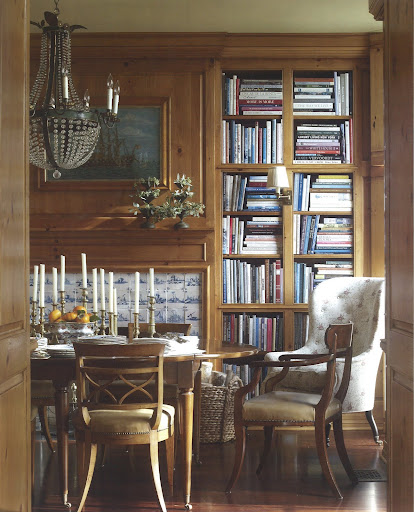 From the Belling House in Newport Bay, California, this dining room also serves as a library.  The mix of pine paneling and the rustic French chandelier brings to the space both