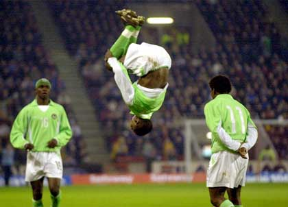 Nigeria's Julius Aghahowa performs a somersault as he celebrates scoring his 2nd goal, during the friendly International soccer match against Scotland at Pittodrie Stadium, Aberdeen, Scotland, Wednesday April 17, 2002. Nigeria won the match 2-1. (AP Photo/PA, Ben Curtis) ** UNITED KINGDOM OUT MAGAZINES OUT - NO SALES **