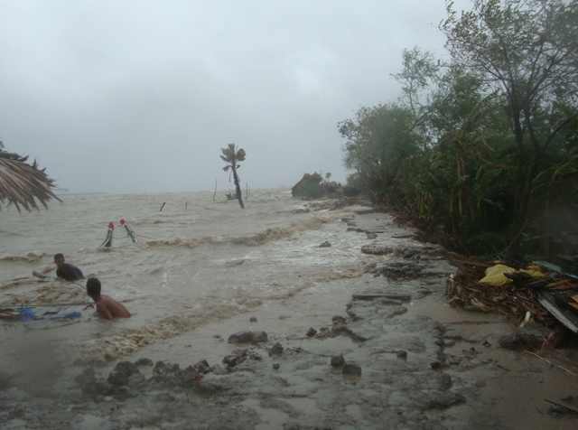 Cyclone Aila, which hit Bangladesh on 25 May 2009, producing a storm surge which in combination with a high tide, forced sea water upriver, breached the embankment that was supposed to protect the population from flooding. The photo shows Mostafa Rokonuzzaman, a young farmer from the village of Tepakhali in south-western Bangladesh, trying to salvage a few possessions from the flood water. OXFAM