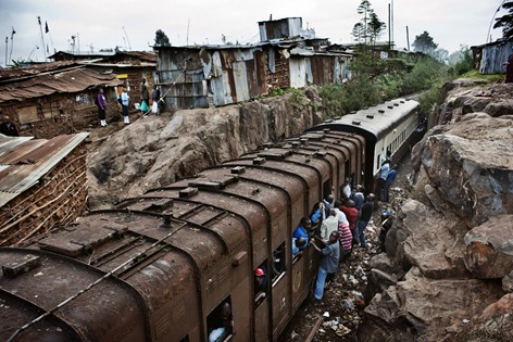 Kibera, Kenya. 6 July 2011<br /><br />A train slows down as it passes through the slum. The Uganda Railway Line - built at the time of the British colonial rule and known locally as 'The Lunatic Express' - passes through the centre of Kibera. Shacks are tightly packed together and the railway is the main thoroughfare for the slum residents, who often walk along the rails. There is a railway station in Kibera, though trains don't stop but keep moving at a slow pace to let people hop on and off. <br />