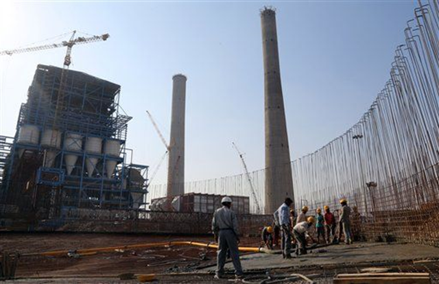 In this 24 February 2015 photo, workers lay cement to build a concrete structure at the under-construction coal-fired power plant, partially financed by the Japan Bank for International Cooperation, in Kudgi, India. Despite mounting protests, Japan continues to finance the building of coal-fired power plants with money earmarked for fighting climate change, with two new projects underway in India and Bangladesh, The Associated Press has found. Photo: Aijaz Rahi / AP