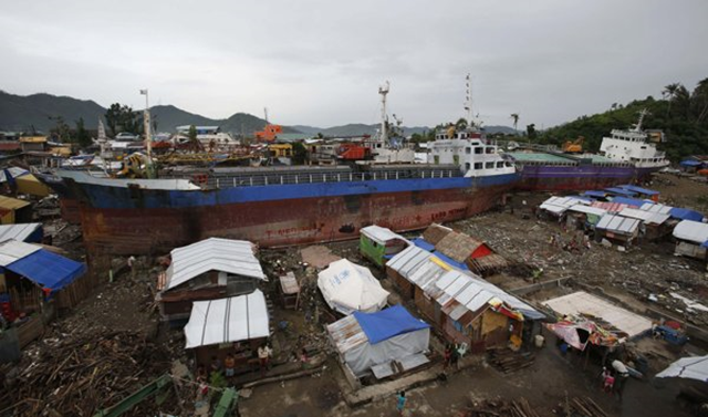 Typhoon survivors living in temporary shelters are seen near ships that ran aground, nearly 100 days after super Typhoon Haiyan devastated Tacloban city in central Philippines 14 February 2014. Typhoon Haiyan killed more than 6,200 people and left tens of thousands homeless when it struck in November last year. Photo: Erik De Castro / REUTERS