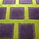 Tkanina obiciowa, trudnopalna. Pluszowa. Motyw geometryczny - krata. Zielona, fioletowa.