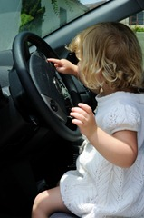 Little girl sits in a car and plays with the steering wheel, pretending to drive.