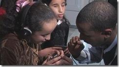Homem explica a uma criança  cega e outra com baixa visão como usar os fones de ouvido