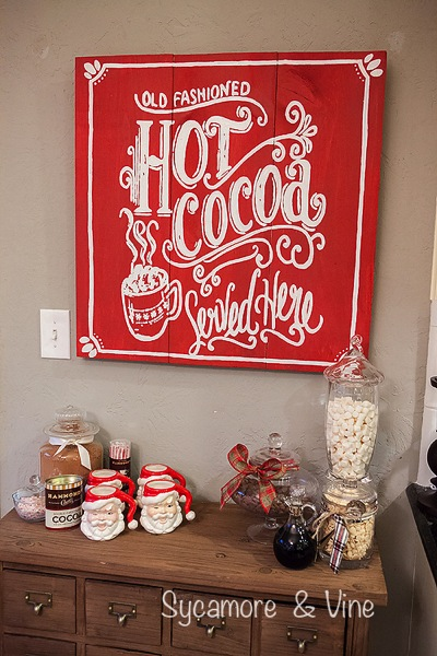 Old Fashioned Hot cocoa served here Sign above a cocoa hot chocolate bar. A truly stunning Christmas Home Tour as part of the Christmas in the Country Blog Tour. This Plaid Inspired Country Christmas will knock your socks off. Features tours of the Living room, Dining Room and a Cocoa hot chocolate bar in the Breakfast room. There is so much inspiration for Christmas decorations in this one post. Be prepared to feel like you are cuddled up by the fire in a warm Northwoods comfy cottage! #country #Christmas #Plaid #Holiday decorating #Holiday ideas #Holidays #Christmas decor #Holiday decor