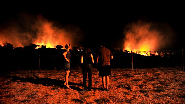 Alice Springs, Australia residents watch a bush fire blazing near homes, in September 2011. Picture: Chloe Geraghty / The Advertiser