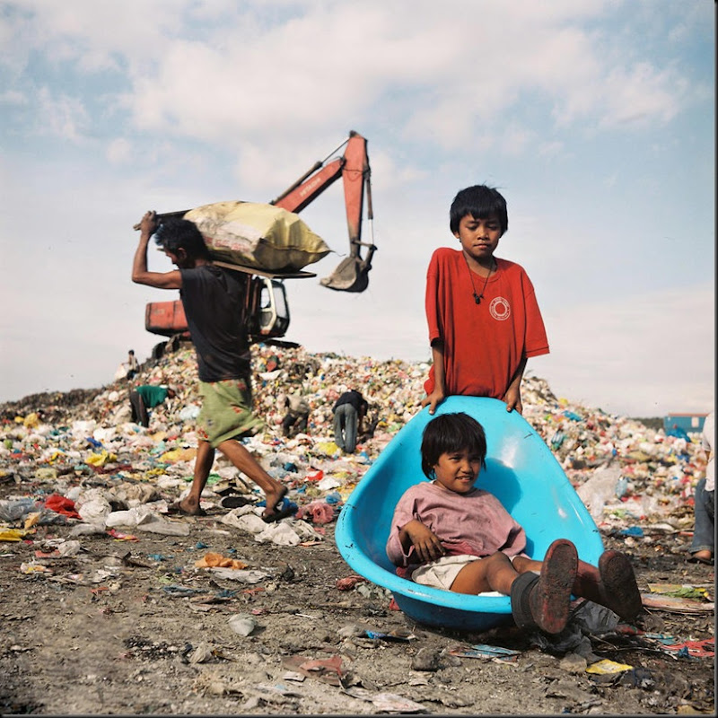 Two kids try to mix play with work inside Happyland, a large garbage dump in Manila. Several of the scavengers inside the complex are out-of-shool children who are forced to do their parents' work in order to augment the daily income. Scavengers earn a measly eighty pesos (USD 2.00) for a day's work.