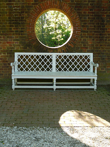 A perfect circle void in the garden wall offset by the geometry of the bench. This is classic, timeless garden design.