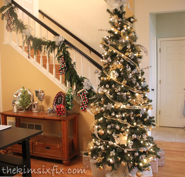 Christmas tree at base of stairs