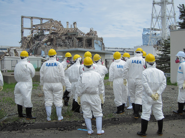 Members of the International Atomic Energy Agency (IAEA) team look at the No.3 reactor building at Tokyo Electric Power Co.'s (Tepco) Fukushima Dai-Ichi nuclear power station in Fukushima, Japan, in this handout photograph released to the media on Friday, May 27, 2011. Source: Tokyo Electric Power Co. via Bloomberg