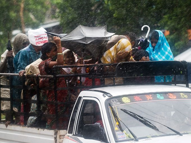 Villagers try to cover themselves from heavy rainfall and strong winds as they ride a pickup in Srikakulam district on Saturday, 12 OCtober 2013. India evacuated over 600,000 people as the massive cyclone Phailin closed in. Photo: Manan Vatsyayana / AFP / Getty Images
