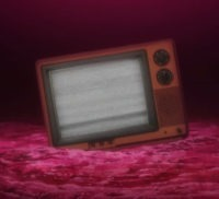 An old knob-switch style TV sits awkwardly in red looking dirt displaying white-noise snow
